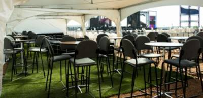 Event rentals cruiser table with upholstered stools in VIP tent