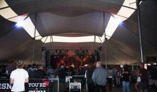 Event tent rental of festival pole tent with concert stage, VIP platform seating and custom bars for