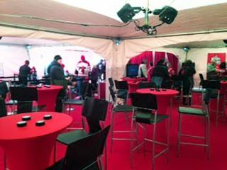 Outdoor events provide lounges in tent rentals with covered cruiser tables and black leather stools.