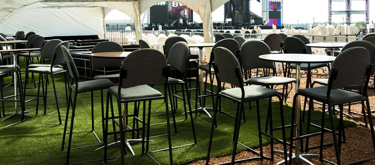 Event Rentals cruiser table with upholstered stools in VIP beer tent